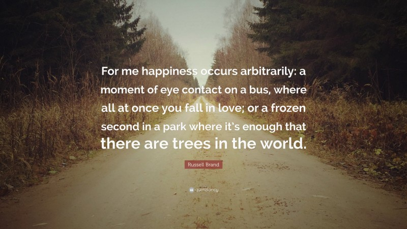 """Russell Brand Quote: """"For me happiness occurs arbitrarily: a moment of eye contact on a bus, where all at once you fall in love; or a frozen second in a park where it's enough that there are trees in the world."""""""