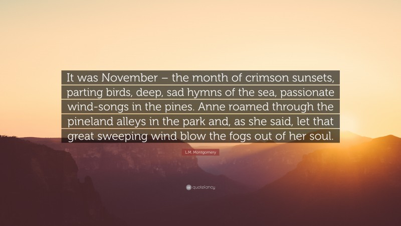 """L.M. Montgomery Quote: """"It was November – the month of crimson sunsets, parting birds, deep, sad hymns of the sea, passionate wind-songs in the pines. Anne roamed through the pineland alleys in the park and, as she said, let that great sweeping wind blow the fogs out of her soul."""""""